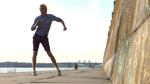 Energetic Man Dances Disco on a Riverbank With a High Stone Wall in Slo-Mo Footage