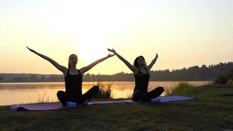 Two Girls Sit on Mats in Semi-Lotus Pose on a Lake Bank at Sunset in Slo-Mo Image