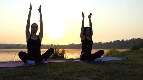Two Women Sit on Mats, Raise Arms Up, Relax at a Yoga Pose at Sunset in Slo-Mo Live Action