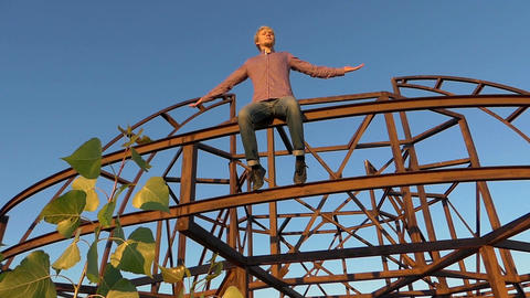Young man sits on a metallic construction at sunset in slo-mo Footage