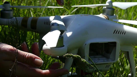 A modern quadracopter is fixed with female hands in summer Footage