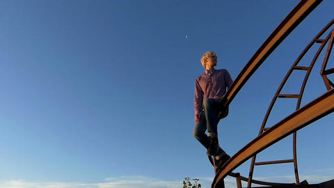 Romantic man sits on a metallic construction at sunset in slo-mo Image