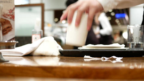 Pan shot of worker cleaning table after customer eating food inside restaurant Footage