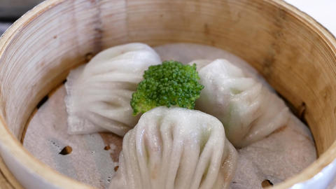 Motion of steamed vegetarian dumplings with steam inside Chinese restaurant with Live Action