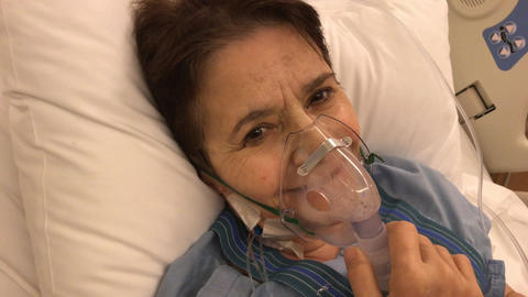 female patient wearing oxygen mask in bed after cardiac surgery 画像