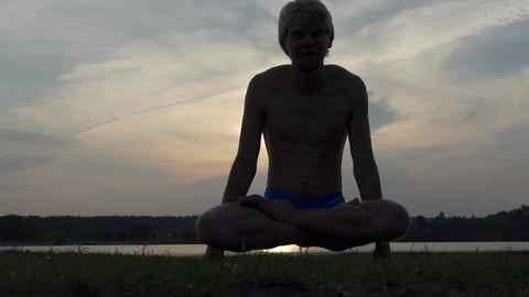 Yogi man sits in a lotus and raises his body at sunset in slo-mo Footage