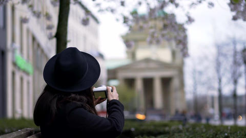 Girl/Woman filming/photographing Brandenburger Tor between flowers in Berlin Footage