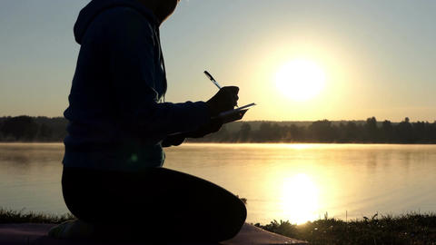 Woman writes something in her notepad at sunset in slo-mo Footage