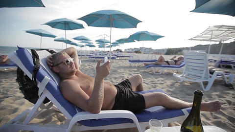 young man lying on a sun lounger on the beach and she can text on a mobile phone Footage