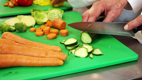 Chef chopping vegetables on green board Footage
