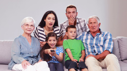 Extended family watching tv while changing channels Footage