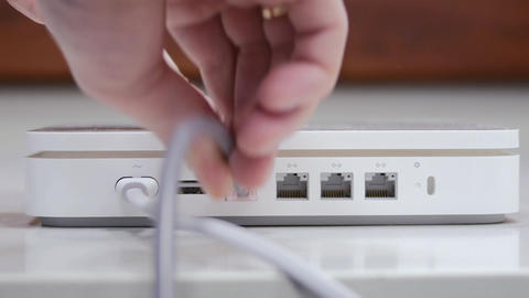 hand plug in ethernet cable in white router Footage