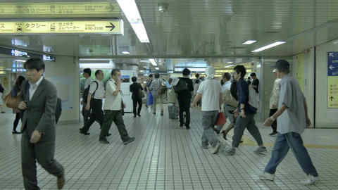 Commuters rush through one of the busiest subway stations in Tokyo at Shinjuku Footage