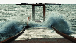 Video - Big waves hit the concrete pier and causing water splashes that flood th Footage
