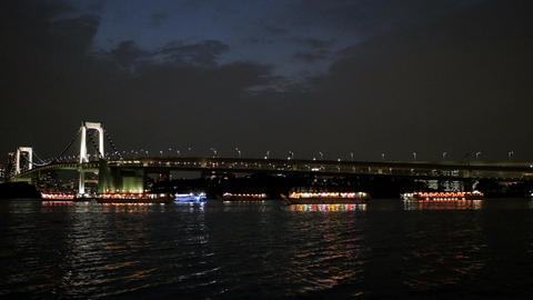 Illuminated party boats gathering off the shore at Odaiba Footage