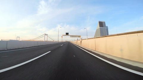 Driver's point of view across the bridge towards the climbing sunshine over the  Footage