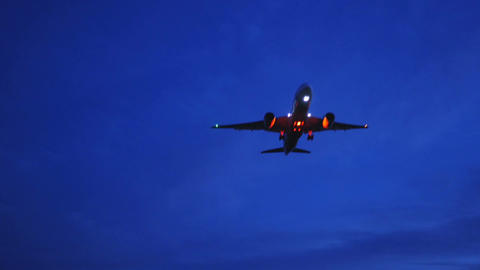 A modern jet with red flashing lights approaching landing at twilight. (with sou Footage