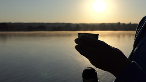 4k - Female hand keeps a cup of coffee on a lake bank at sunset 画像