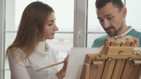 Young couple discuss some moments of future picture during drawing Footage