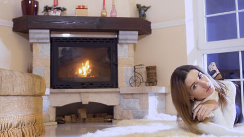 Young girl lays on floor near the fireplace Footage