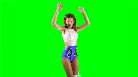 Beautiful fit girl dancing to the music in headphones at green background Footage
