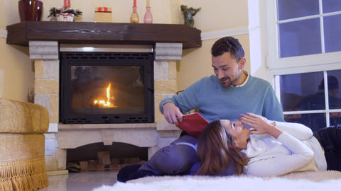 Husband read the book to his wife, happy married couple relaxing near fireplace Footage