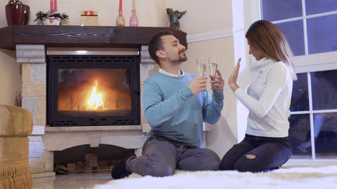 Girl shows pregnancy test to husband sitting on floor near fireplace Footage