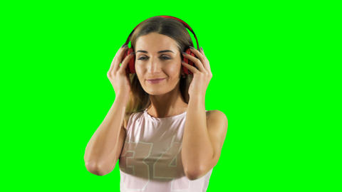 Smiling blonde enjoys of listening music in headphones at green background Footage