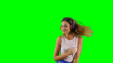 Stylish girl in headphones listens music and dance at green background Footage