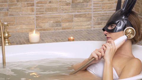 Sexy bunny girl takes a hot bath with aroma candles Footage