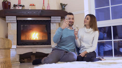 Happy married couple with champagne near fireplace Footage