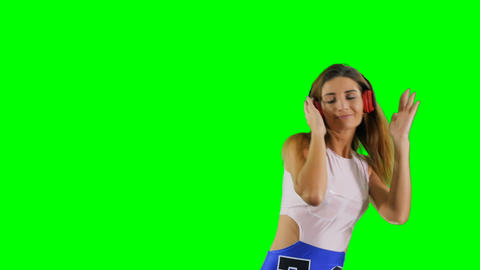 Beautiful energetic girl listen music with headphones at green background Footage