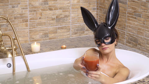 Cute bunny girl drinks tomato juice and relax in hot bath Footage