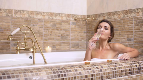 Beautiful lady enjoys of drinking champagne in a hot bath Footage
