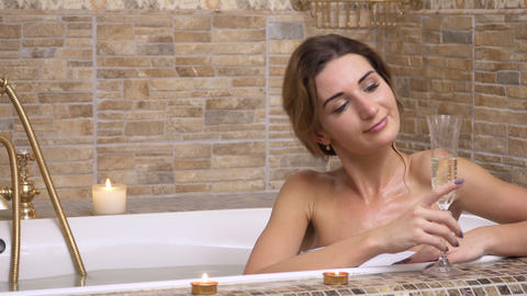 Young beautiful woman drinks champagne relaxing in a hot bath Footage