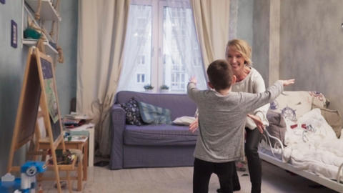 Little boy runs to his mother, they embrace and whirl Live Action
