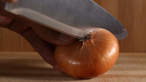 Cutting in half one golden onion Footage