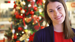 Portrait of cheerful young woman near decorated Christmas tree. Pretty female Footage