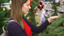 Woman buying Christmas decorations. Female choosing Christmas wreath. Christmas Footage