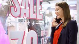 Woman near window shop. Sale sign. Female joyfully talking on phone, telling Footage