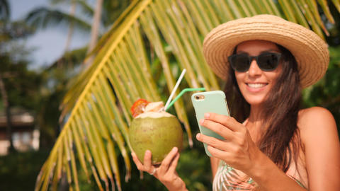 Young Happy Mixed Race Tourist Girl Texting on Mobile Phone and Drinking Coconut Footage