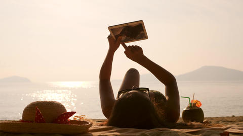 Young Tourist Girl Using Mobile Tablet Gadget and Sunbathing on Tropical Footage