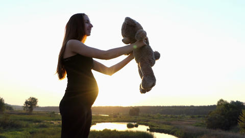 Pregnant woman playing with toy at sunset Footage