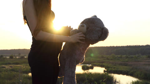 4k - Pregnant woman play with bear at sunset Filmmaterial