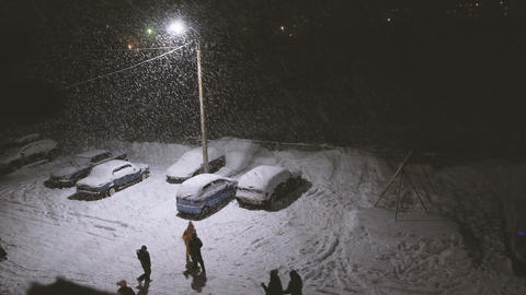 Children playing in the street in heavy snow under the streetlights ビデオ