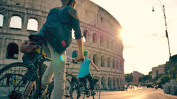 Friends riding bicycles in front of Colosseum in Rome ビデオ