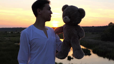 Beautiful sunset with man who plays with big toy bear in slow motion 画像