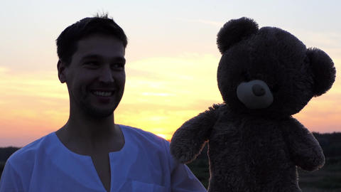 Funny man play with big bear toy at sunset 画像