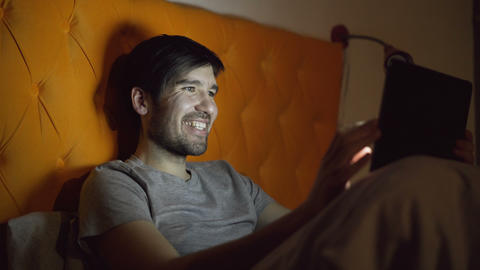 Young laughing man using tablet computer for surfing social media lying in bed Footage