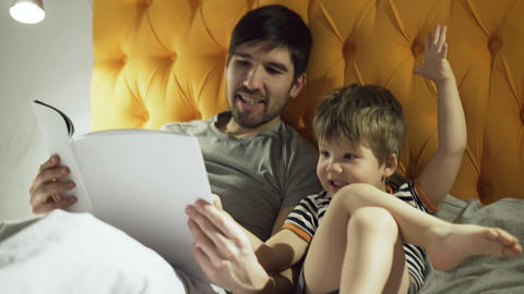 Young father with little son lying on bed at home and reading fairytale book Footage